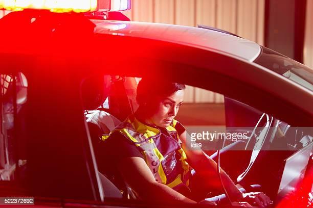 Femme policier assis dans la voiture à l'aide d'ordinateur patrouille