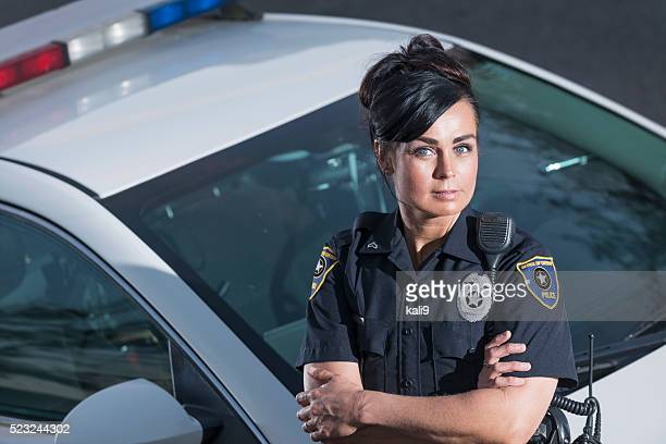 Policewoman standing next to police car, arms crossed