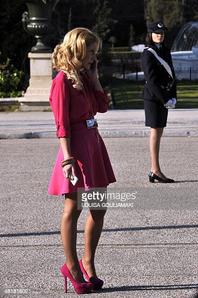 A policewoman stands guard as a journalist talks on a mobile phone during the arrivals of ministers for the Informal Meeting of Ministers for...