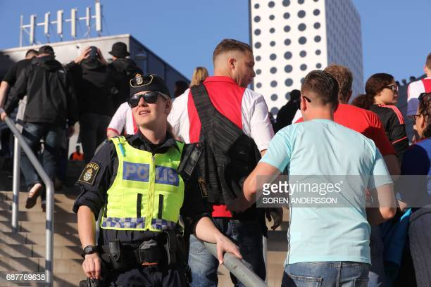 A policewoman stands guard as supporters arrive at the stadium prior to the UEFA Europa League final football match Ajax Amsterdam v Manchester...