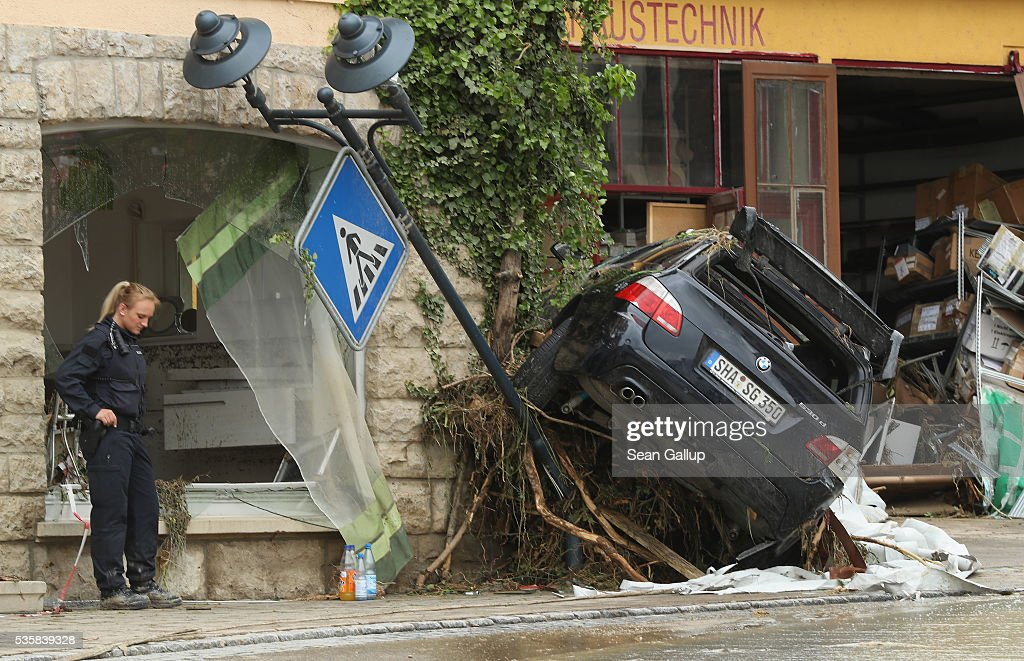 A policewoman stands near a car smashed against a building in the village center following a ferocious flash flood the night before on May 30 2016 in...