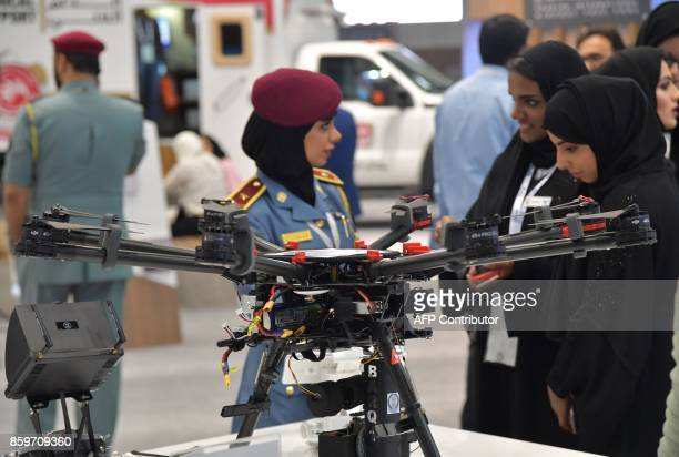A policewoman stands next to a police drone at the Gitex 2017 technology exhibition at the Dubai World Trade Center in Dubai on October 10 2017 / AFP...