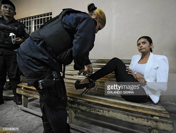 A policewoman takes shackles off former Miss Honduras Belgica Nataly Suarez to enter a courtroom in Tegucigalpa on July 12 2011 The former beauty...