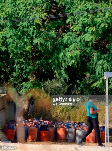 A policewoman walks past dozen of gas bottles in Alcanar during a search linked to the Barcelona and Cambrils attacks on the site of an explosion on...