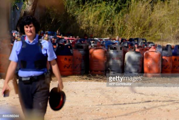 A policewoman walks with dozen of gas bottles in background in Alcanar during a search linked to the Barcelona and Cambrils attacks on the site of an...