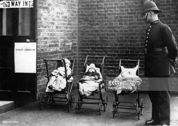 Policier surveillant trois enfants dans leurs poussettes à l'entrée d'un bureau de vote lors d'une élection locale