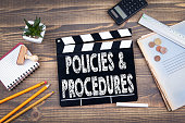 Policies and Procedures. movie clapper on a wooden desk