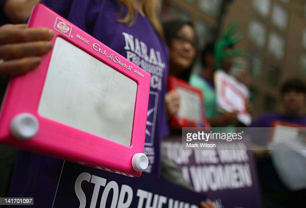 NARAL policy aide Kate Vlach holds a 'Etch A Sketch' while participating in a protest outside of the Hyatt Regency where Republican presidential...