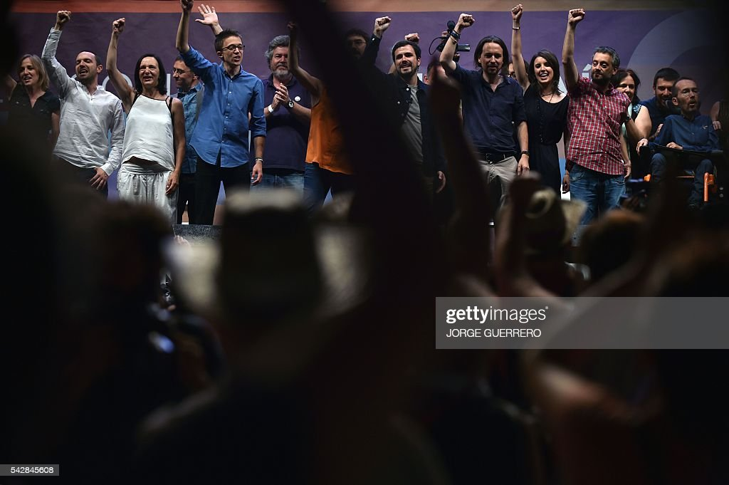 Policy secretary of left-wing party Podemos Inigo Errejon (4L) Leader of left wing party Podemos and party candidate Pablo Iglesias (4R), left-wing party IU leader Alberto Garzon (C) and party members raise their fists during the partys final campaign meeting in Madrid on June 24, 2016 ahead of the June 26 general election. Spain votes again on June 26, six months after an inconclusive election which saw parties unable to agree on a coalition government. GUERRERO