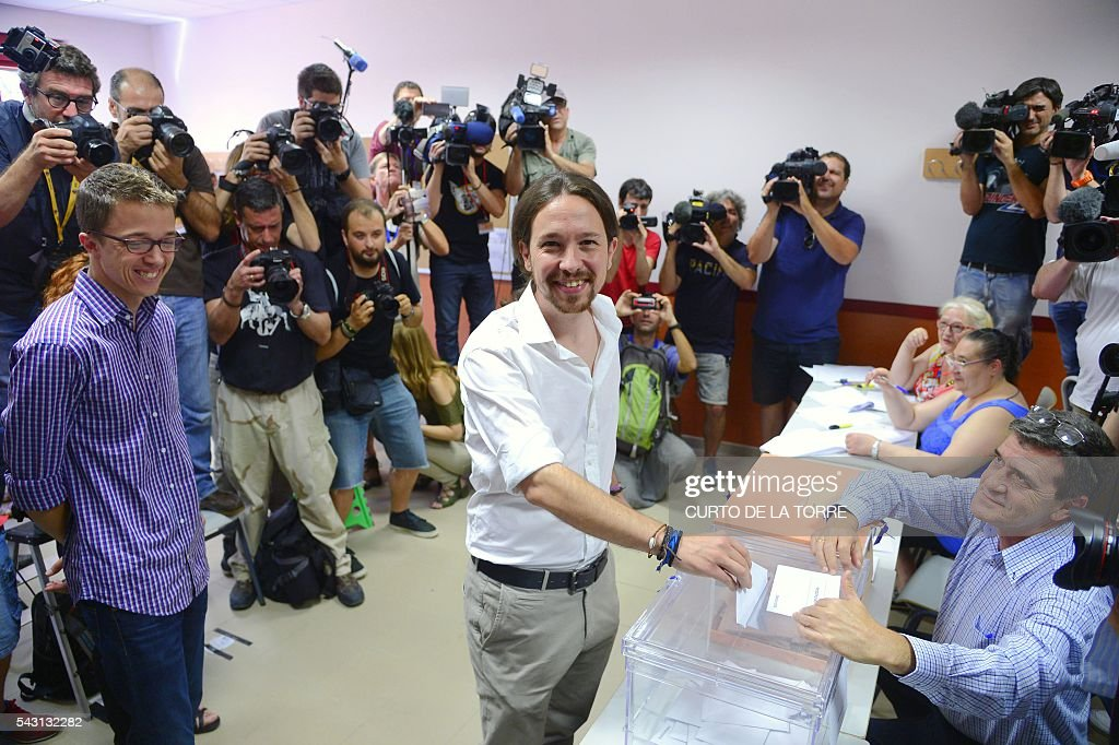 Policy secretary of left-wing party Podemos Inigo Errejon (L) watches Leader of left wing party Podemos and party candidate, Pablo Iglesias, (C) vote in Spains general election at a polling station in cental Madrid on June 26, 2016. Spain votes today, six months after an inconclusive election which saw parties unable to agree on a coalition government. TORRE
