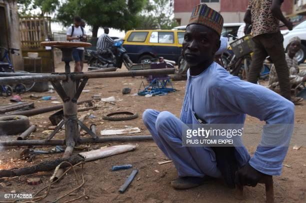 A polio victim arrives in his welding workshop in Kano northwest Nigeria on April 21 2017 The World Health Organization said 116 million children are...