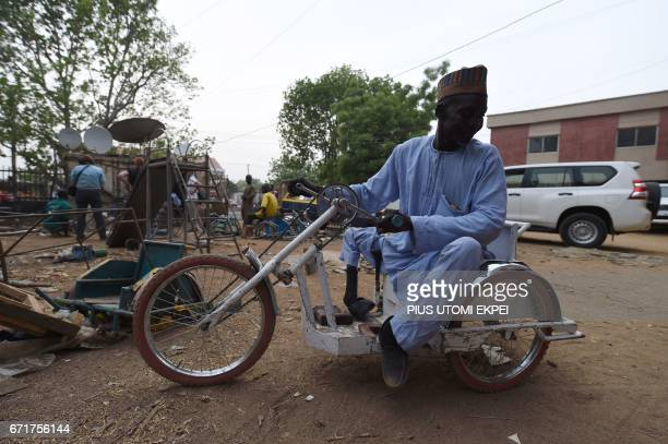 A polio victim sits on a locally fabricated tricycle in his workshop Kano northwest Nigeria on April 21 2017 The World Health Organization said 116...