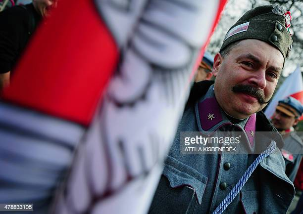 A Polish activist wearing a historic uniform poses for a photograph ahead of the official ceremony in front of the National Museum of Budapest on...