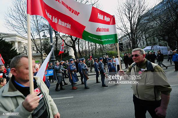 Polish activists wearing historic uniforms prepare for the official ceremony in front of the National Museum of Budapest on March 15 2014 during the...