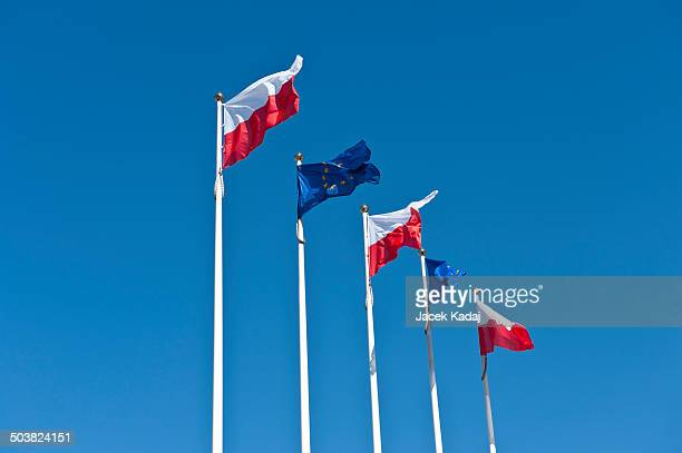 Polish and EU flags on sky background