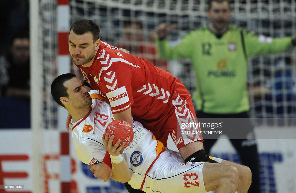 Polish Bartosz Jurecki (R) fights for the ball with Macedonian Filip Lazarov (L) on January 23, 2012 during the men's Euro 2012 Handball Championship match at the Belgrade Arena. AFP PHOTO / ATTILA KISBENEDEK