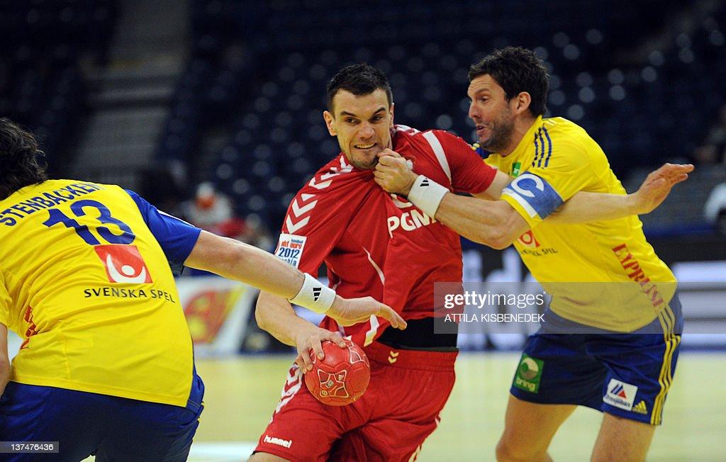 Polish Bartosz Jurecki (C) vies for the ball with Swedish Tobias Karlsson (R) and Jonathan Stenbacken (L) during the Men's EHF Euro 2012 Handball Championship match between Poland and Sweden, on January 21, 2012, at the Belgrade Arena.