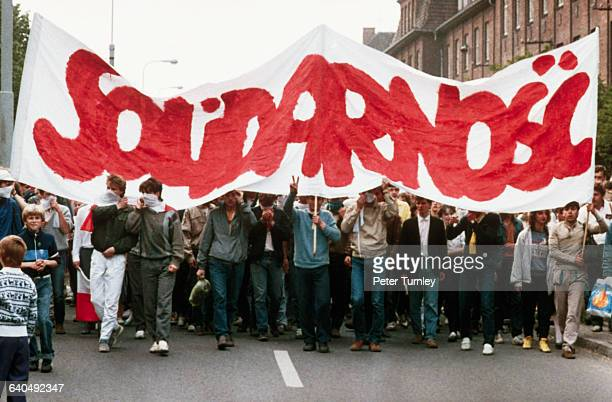 Polish citizens hold a Solidarity banner at a rally during Pope John Paul II's visit in 1987 At the time of the protest the labor union was...