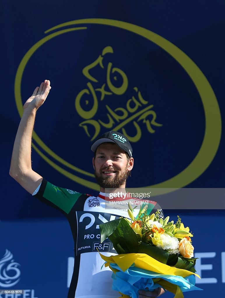 Polish cyclist Marcin Bialoblocki jubilates on the podium after winning the UAE flag jersey for best intermediate sprint classification at the end of the second stage of Dubai Tour 2016 in Dubai on February 4, 2016. Italy's Elia Viviani, riding for Team Sky, sprinted to victory in the second stage of the Tour of Dubai and grabbed the leader's blue jersey from Germany's Marcel Kittel. Viviani had benefitted from a crash in the final kilometre that appeared to affect opponents. NAAMANI