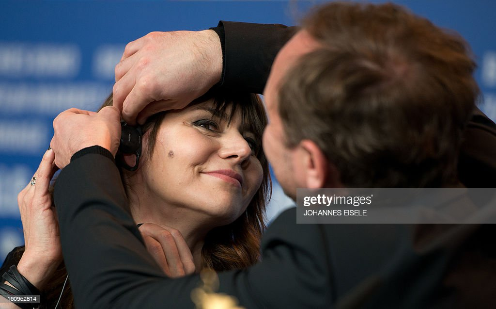 Polish director Malgoska Szumowska is helped with her headphones by Actor Andrzej Chyra during a press conference of their film 'In the Name of' (W imie) at the 63rd Berlinale Film Festival on February 8, 2013.