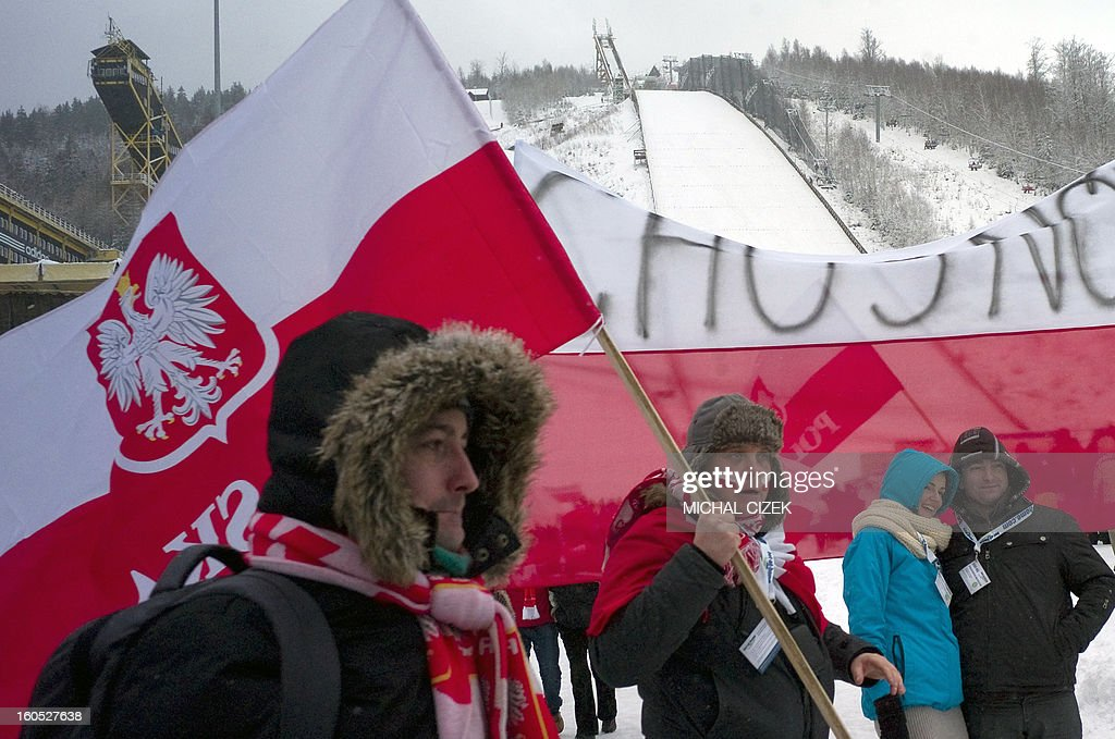 Polish fans holding the their national flags wait for the start of the FIS Ski Jumping World Cup on February 02, 2013 in Harrachov. The day's practice round of Ski Jumping World Cup was delayed due to the weather conditions. AFP PHOTO / MICHAL CIZEK
