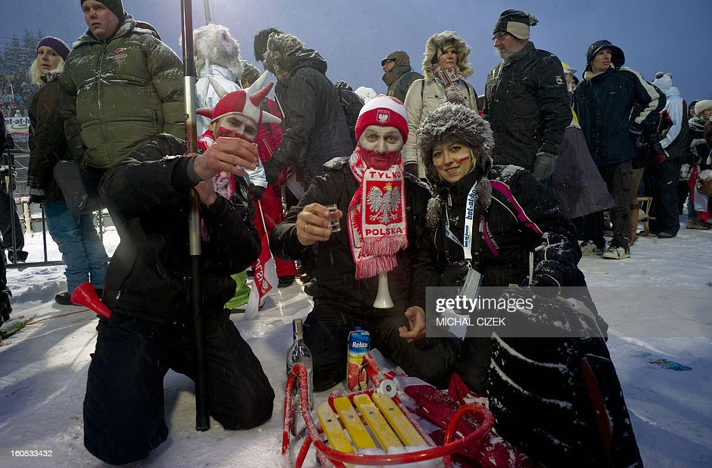 Polish fans pose with shots of vodka as they wait for the start of the Ski Flying event of the FIS Ski Jumping World Cup in Harrachov on February 02, 2013. Today's competition was canceled due to bad wheather conditions.