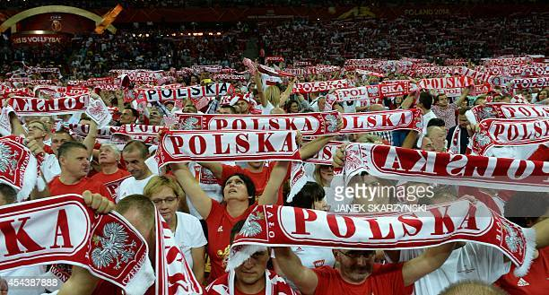 Polish fans wave scarfs during the opening match of the FIVB Mens Volleyball World Championship at the National Stadium in Warsaw on August 30 2014...