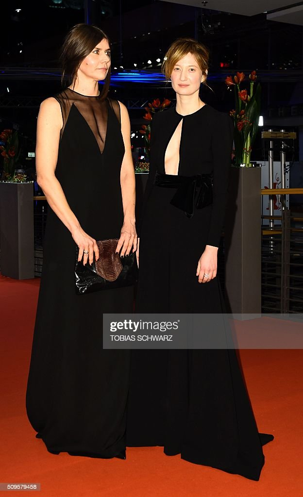 Polish film maker and jury member Ma?gorzata Szumowska and Italian actress and jury member Alba Rohrwacher pose for photographers as he arrives on the red carpet for the film 'Hail, Caesar!' screening as opening film of the 66th Berlinale Film Festival in Berlin on February 11, 2016. Eighteen pictures will vie for the Golden Bear top prize at the event which runs from February 11 to 21, 2016. / AFP / TOBIAS SCHWARZ