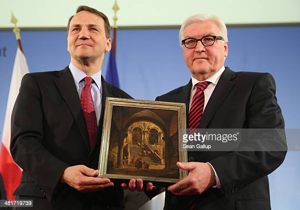 Polish Foreign Minister Radoslaw Sikorski and German Foreign Minister FrankWalter Stenmeier hold the painting 'Palace Steps' by 18thcentury painter...