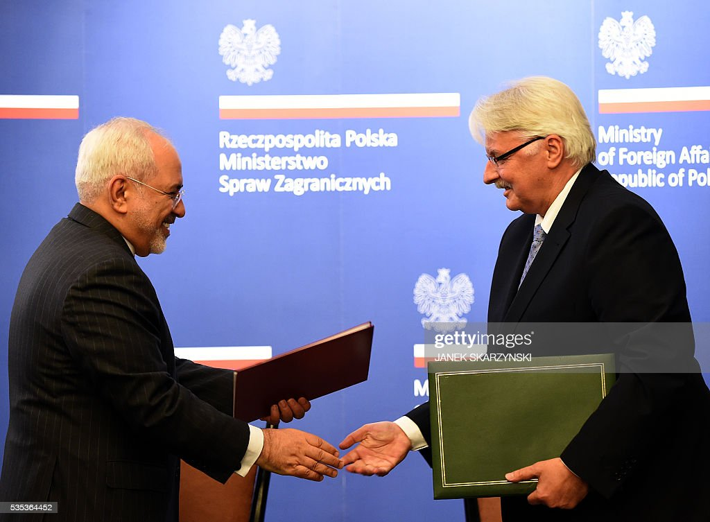 Polish Foreign Minister Witold Waszczykowski (R) exchange documents with Iran's Foreign Minister Mohammad Javad Zarif during their meeting on May 29, 2016 in Warsaw. / AFP / JANEK
