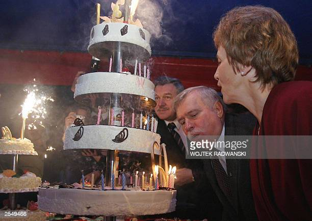 Polish former President Lech Walesa blows off candles on his birthday cake as his wife Danuta watches as he celebates his 60th birthday which was...