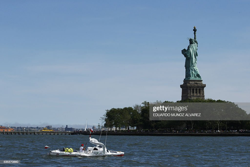 Polish kayaker Aleksander Doba sails next to Statue Liberty at the start of his translatlantic kayak adventure from New York to Lisbon on May 29, 2016 in New York. The 69-year-old man hopes to complete his journey in three months. / AFP / EDUARDO