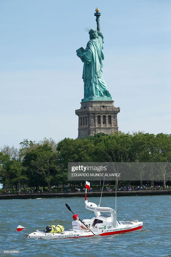 Polish kayaker Aleksander Doba sails next to Statue Liberty at the start of his translatlantic kayak adventure from New York to Lisbon on May 29, 2016 in New York. Doba says this will be his toughest challenge yet, but that he feels like a young man and 'will not pretend to be old.' / AFP / EDUARDO
