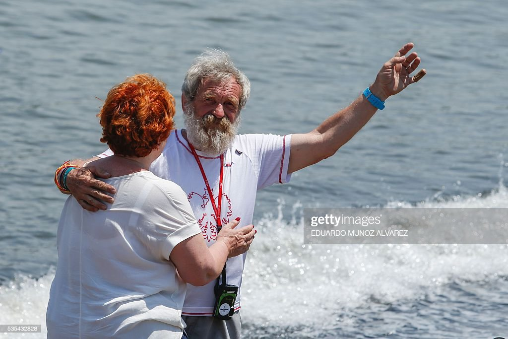 Polish kayaker Aleksander Doba waves to the crowd as he hugs his wife Gabriela Doba before the beginning of his transatlantic kayak adventure from New York to Lisbon on May 29, 2016 in New York. Doba says this will be his toughest challenge yet, but that he feels like a young man and 'will not pretend to be old.' / AFP / EDUARDO