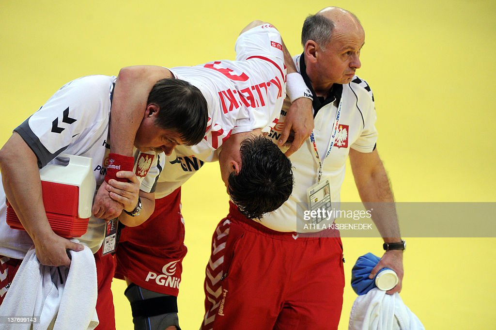 Polish Krzysztof Lijewski (C) is helped by his team members after an injury during the Men's EHF Euro 2012 Handball Championship match Poland vs Germany on January 25, 2012 at the Belgrade Arena.