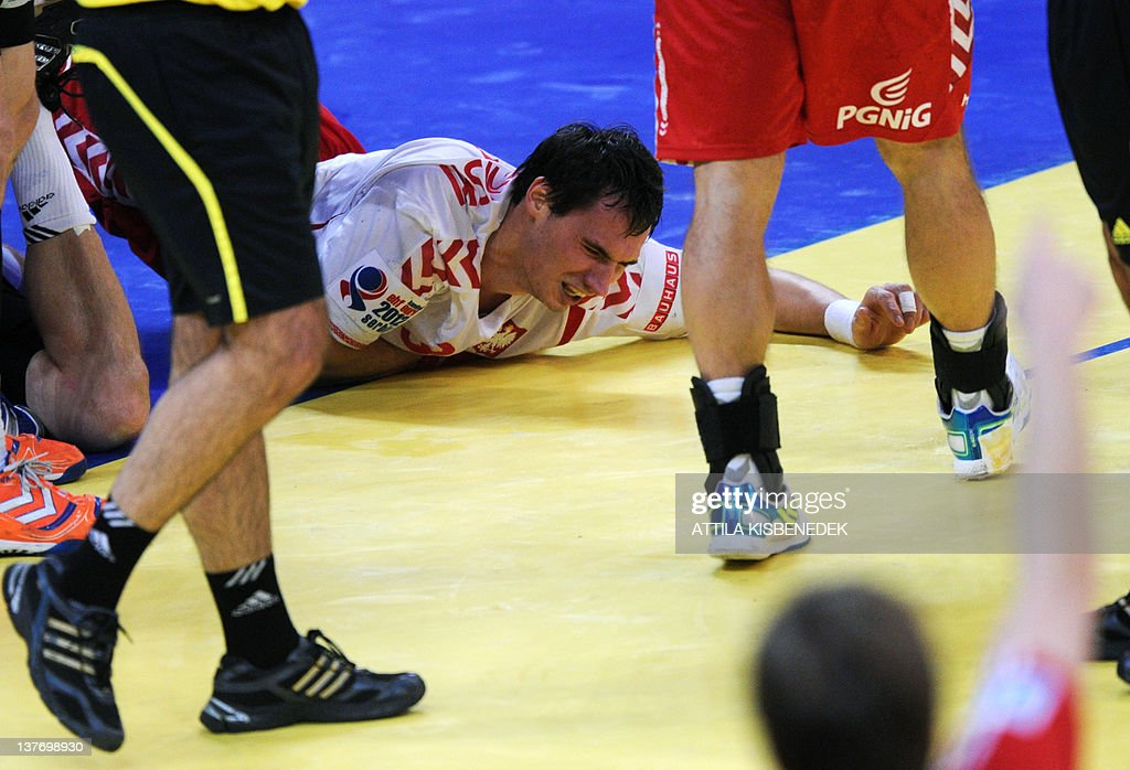 Polish Krzysztof Lijewski (C) lays on the floor after being injured during the Men's EHF Euro 2012 Handball Championship match between Poland and Germany on January 25, 2012, at the Belgrade Arena.