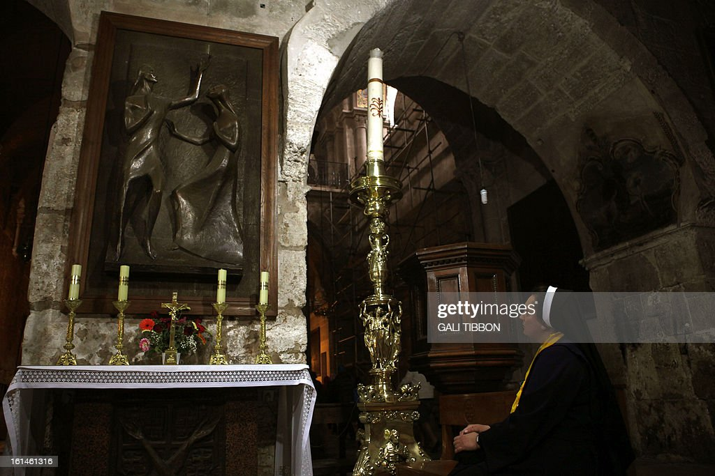A Polish nun prays at the Golgotha as an Orthodox worshiper lights a candle on February 11, 2013 at the Church of the Holy Sepulcher in Jerusalem's Old City. Pope Benedict XVI improved ties between Judaism and Christianity which helped reduced anti-Semitism around the world, the Ashkenazi Chief Rabbi of Israel said following the pontiff's shock resignation. AFP PHOTO/GALI TIBBON