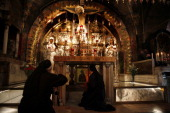 Polish nuns pray at the Golgotha as an Orthodox worshiper lights a candle on February 11 2013 at the Church of the Holy Sepulcher in Jerusalem's Old...