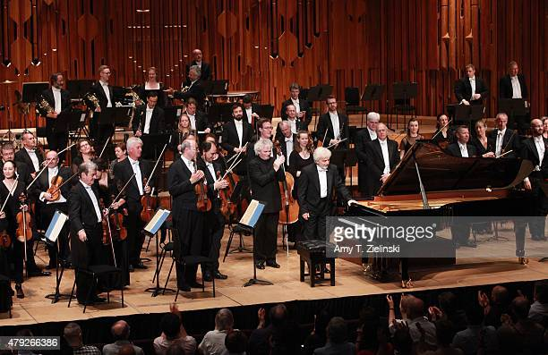 Polish pianist Krystian Zimerman receives applauds with conductor Sir Simon Rattle leading the London Symphony Orchestra after performing Brahms's...