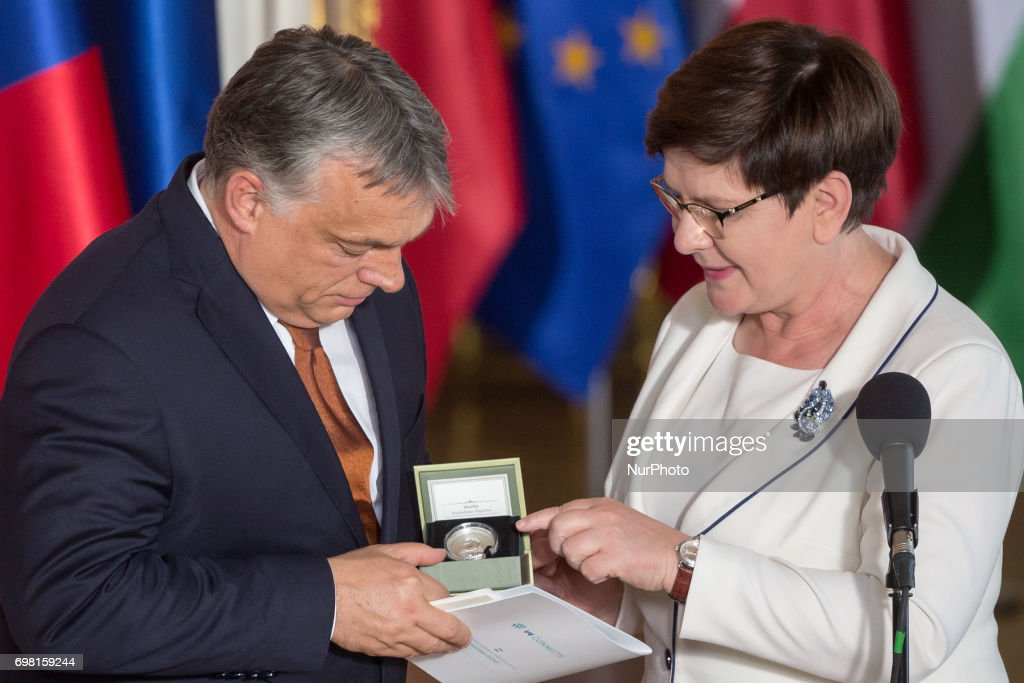 Polish PM Beata Szydlo (R) hands over the presidency of the Visegrad Group to Hungarian Prime Minister Viktor Orban (L) during the Visegrad Group meeting at the Royal Castle in Warsaw, Poland on 19 June 2017