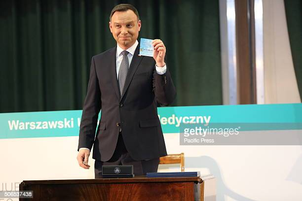 Polish President Andrzej Duda presents his signed organ donation card at the 50th anniversary symposium of the first successful kidney transplant in...