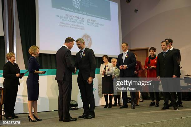 Polish President Andrzej Duda presents Maciej Kosieradski the Golden Cross of Merit during the 50th anniversary symposium of the first successful...