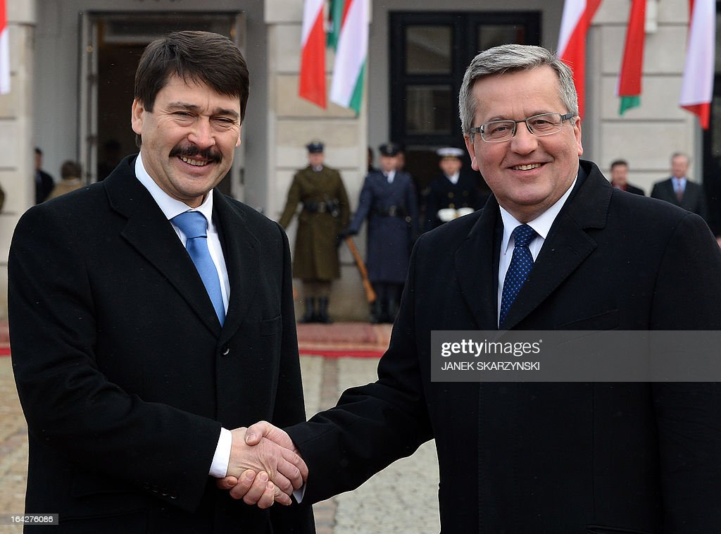 Polish President Bronislaw Komorowski (R) and Hungarian President Janos Ader shake hands in front of the court of presidential palace in Warsaw during an official welcoming ceremony on March 22, 2013. President Ader arrived for an official two-day visit.