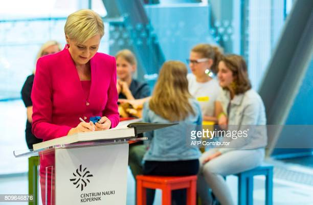Polish President's wife Agata KornhauserDuda signs the Golden Book as she visits the Copernicus Science Center with the US First Lady in Warsaw on...