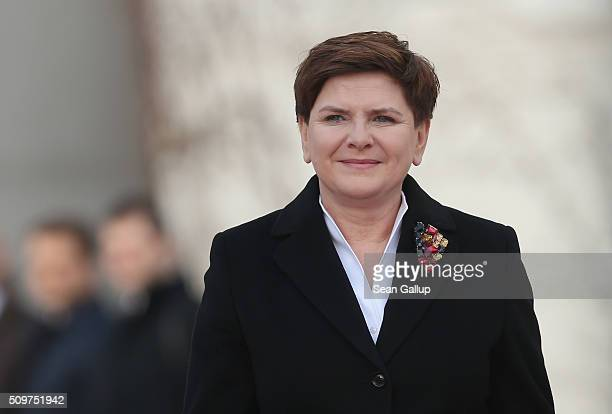 Polish Prime Minister Beata Szydlo accompanied by German Chancellor Angela Merkel prepares to review a guard of honor upon Szydlo's arrival at the...