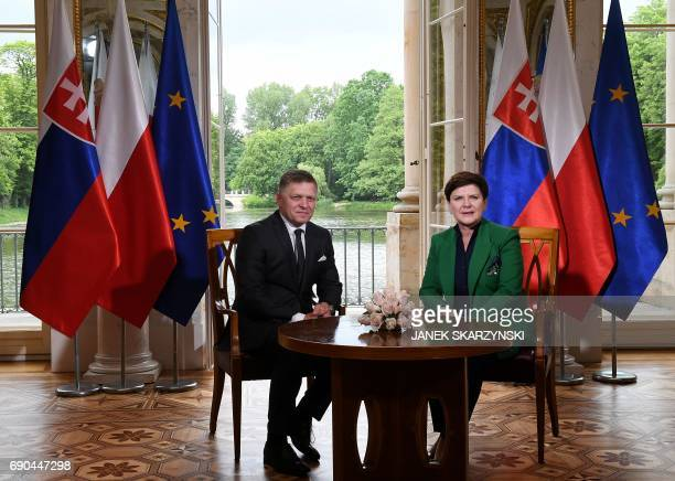 Polish Prime Minister Beata Szydlo and Slovak Prime Minister Robert Fico have taken seat for talks during a meeting at the Palace on the Isle in...