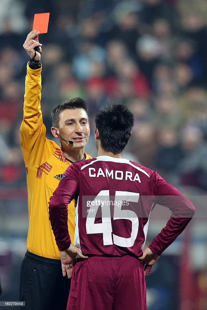 Polish referee Pawel Gil (L) shows red card to Cluj's Portuguese defender Camora (R) during the UEFA Europa League Round of 32 football match CFR 1907 Cluj vs Inter Milan in Cluj, northern Romania on February 21, 2013.