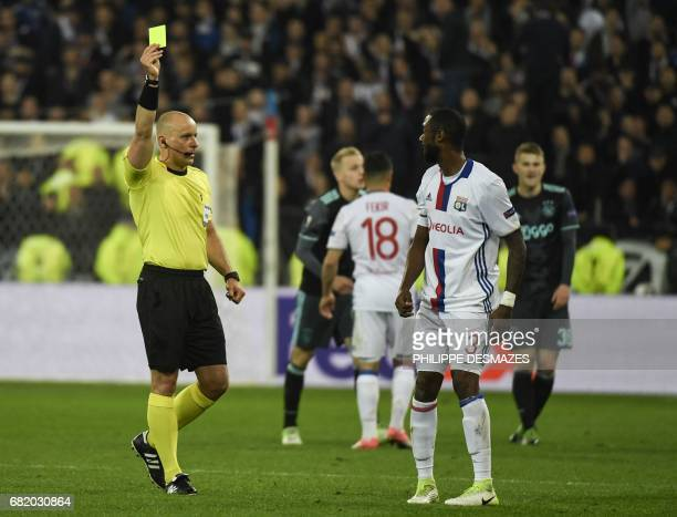 Polish referee Szymon Marciniak gives a yellow card to Lyon's French Cameroonian defender Nicolas Nkoulou during the UEFA Europa League semifinal...
