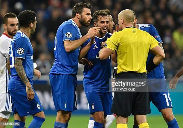 Polish referee Szymon Marciniak listen to Juventus' players during the Champions League football match between Olympique Lyonnais and Juventus on...
