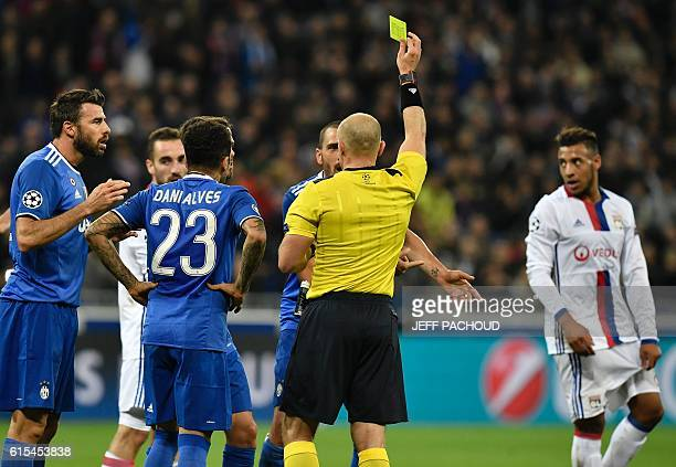 Polish referee Szymon Marciniak shows a yellow card during the Champions League football match between Olympique Lyonnais and Juventus on October 18...